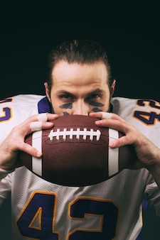 Retrato de jogador de futebol americano, segurando uma bola e olhando