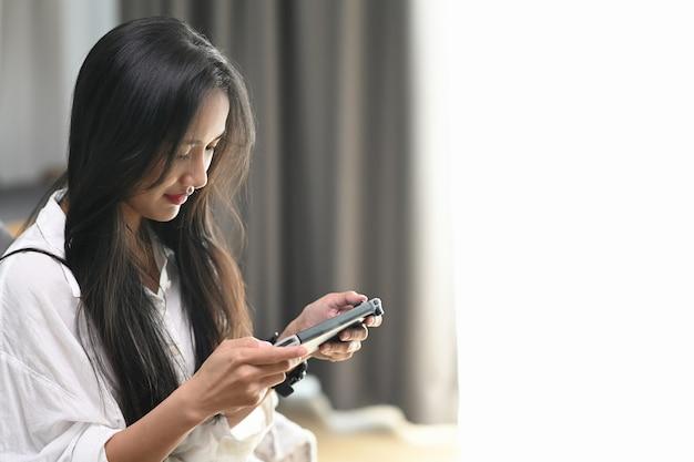 Retrato de jogador feminino jogando videogame e sentado no sofá em casa.