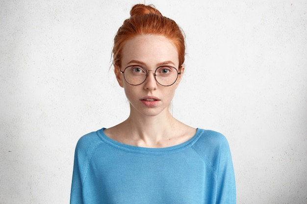 Retrato de jornalista séria ruiva usa óculos e suéter azul, tem pele sardenta, pensa em nova publicação com expressão pensativa
