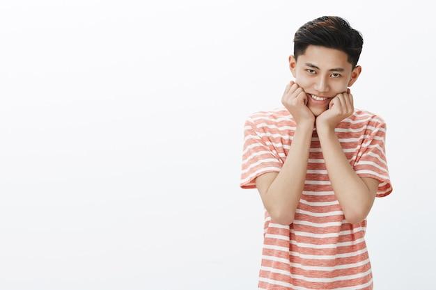 Retrato de jovem adolescente bobo e fofo asiático em camiseta listrada, sorrindo, inclinando a cabeça nas palmas das mãos pressionadas contra o queixo tentando parecer doce e terno