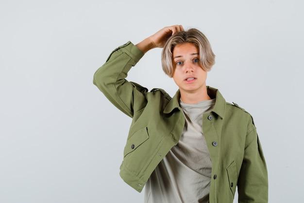 Retrato de jovem adolescente coçando a cabeça com uma jaqueta verde e olhando a vista frontal esquecida