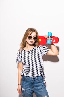 Retrato de jovem adolescente em óculos de sol posando com skate em pé sobre uma parede branca