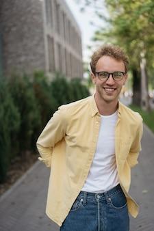 Retrato de jovem adolescente sorridente usando óculos elegantes de camisa casual e andando na rua