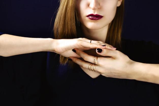 Retrato de jovem adulto branco usando batom de ameixa escura e segurando as mãos com manicure escuro juntos na frente do pescoço. .