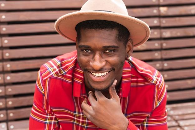 Retrato de jovem adulto de camisa vermelha e chapéu