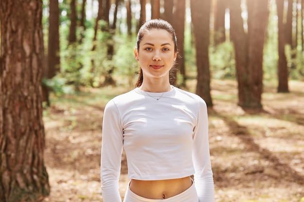 Retrato de jovem adulto feminino atraente de cabelos escuros em roupas esportivas elegantes, posando na floresta, antes ou depois do treino