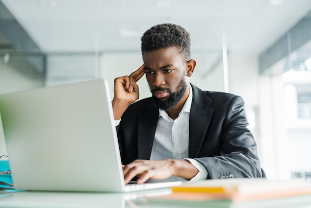 Retrato de jovem africano digitando no laptop no escritório