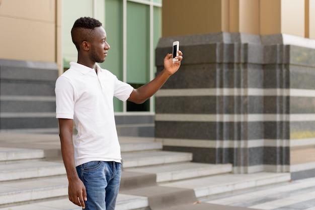 Retrato de jovem africano em edifício moderno ao ar livre da cidade