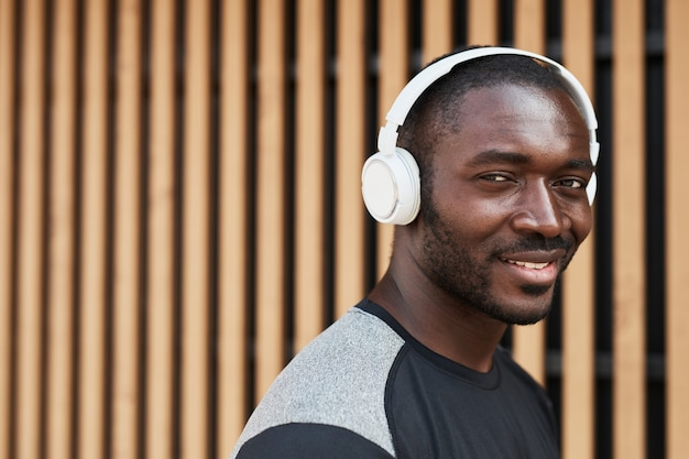 Retrato de jovem africano em fones de ouvido sem fio, sorrindo para a câmera enquanto caminha pela cidade