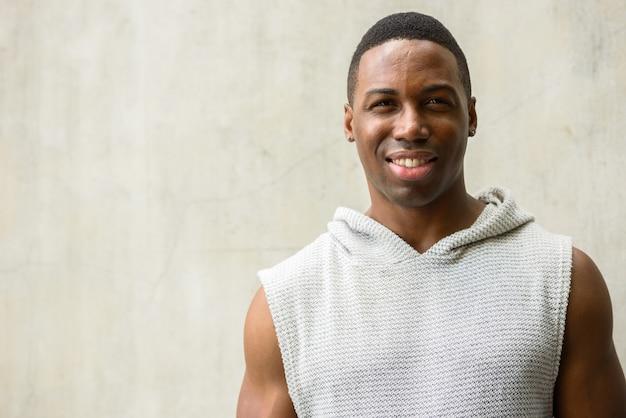 Retrato de jovem africano musculoso e bonito pronto para a academia contra uma parede de concreto ao ar livre