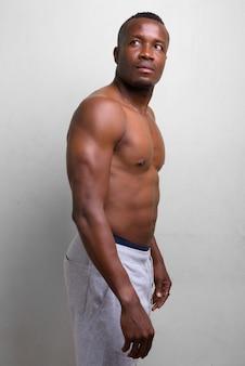 Retrato de jovem africano musculoso sem camisa em branco