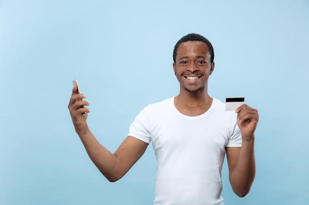 Retrato de jovem afro-americano de camisa branca, segurando um cartão e um smartphone.