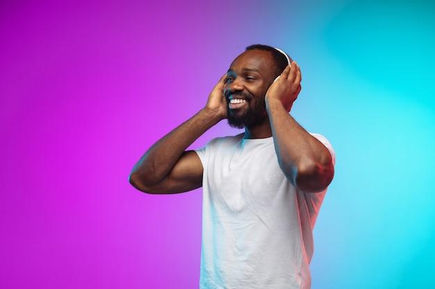 Retrato de jovem afro-americano em estúdio gradiente em néon