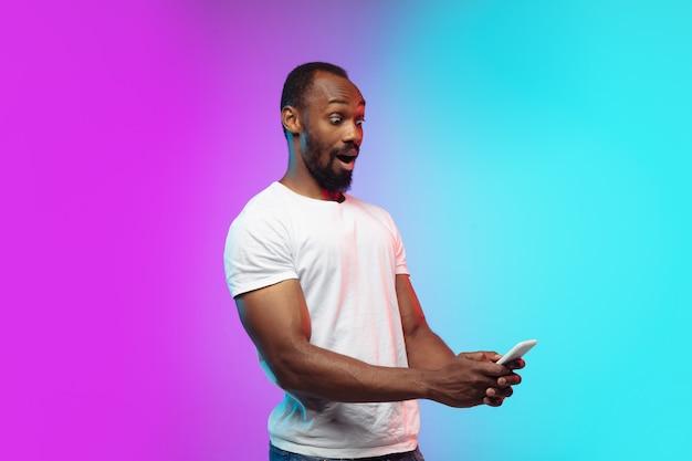 Retrato de jovem afro-americano em estúdio gradiente em neon