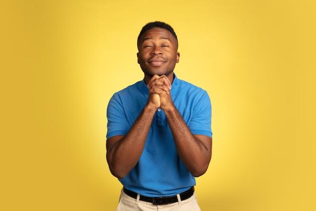 Retrato de jovem afro-americano isolado no fundo amarelo do estúdio, expressão facial.