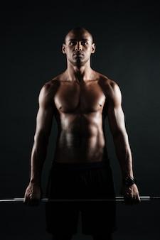 Retrato de jovem afro-americano musculoso segurando barra