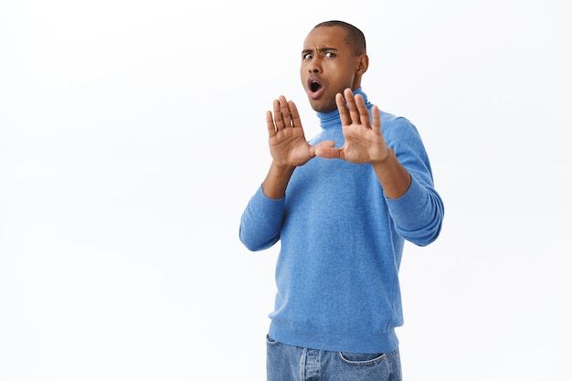 Retrato de jovem afro-americano, nervoso e relutante, dizendo para ficar longe de mim, fazendo bloqueio com as mãos levantadas, gesto de pare