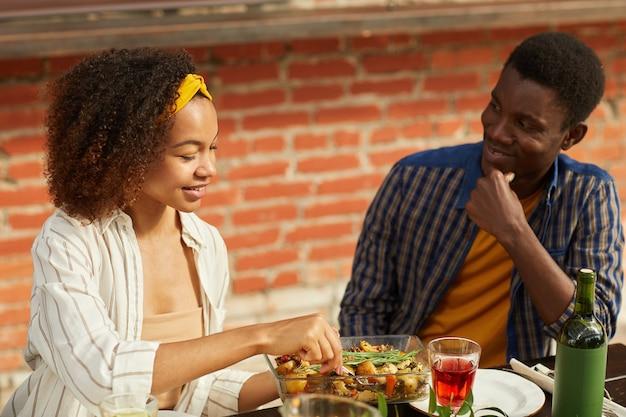 Retrato de jovem afro-americano olhando para uma linda mulher enquanto jantava com amigos sentados à mesa ao ar livre durante a festa de verão