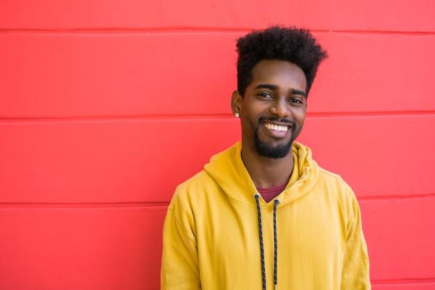 Retrato de jovem afro-americano parecendo confiante e posando contra uma parede vermelha