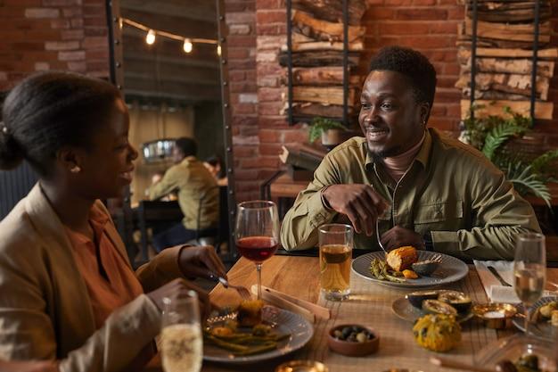 Retrato de jovem afro-americano sorrindo para girlfried enquanto aprecia um jantar ao ar livre