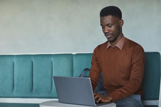 Retrato de jovem afro-americano usando laptop enquanto está sentado no sofá em um escritório de coworking ou biblioteca, copie o espaço