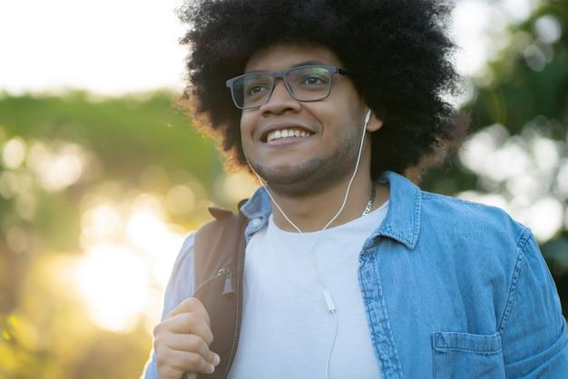 Retrato de jovem afro-latino ouvindo música com fones de ouvido enquanto caminha ao ar livre na rua