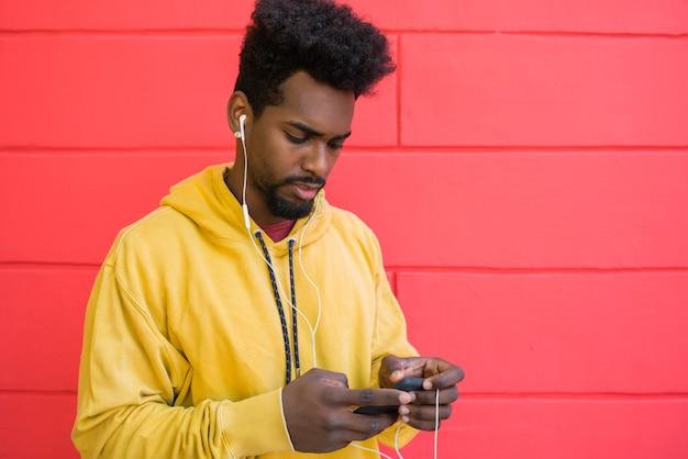 Retrato de jovem afro usando seu telefone celular com fones de ouvido contra a parede vermelha. conceito de tecnologia e estilo de vida.