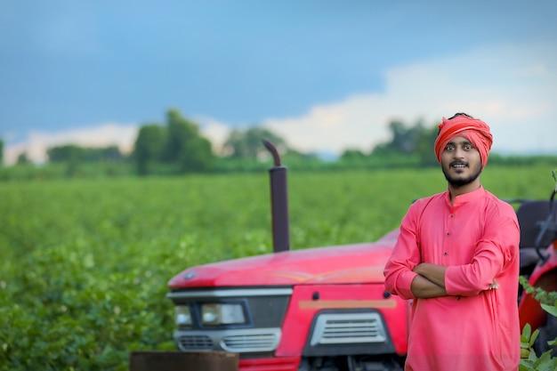 Retrato de jovem agricultor indiano no campo com trator
