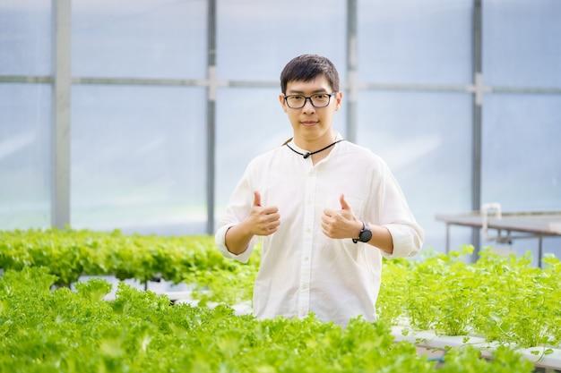 Retrato de jovem agricultor inteligente usando computador tablet digital para inspeção. usando tecnologia na aplicação de campo de agricultura na atividade de cultivo agrícola e verificando o conceito de qualidade.