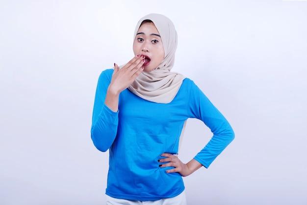 Retrato de jovem alegre com camiseta azul usando hijab, sentindo sono e bocejando