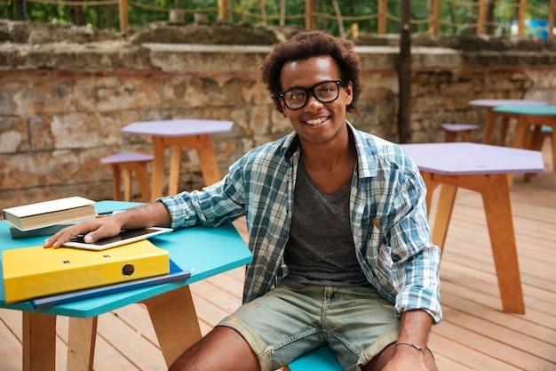 Retrato de jovem alegre de óculos sentado e sorrindo em uma cafeteria ao ar livre