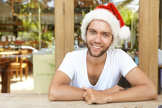 Retrato de jovem alegre e feliz com a barba por fazer vestida de chapéu vermelho com pelo branco se divertindo