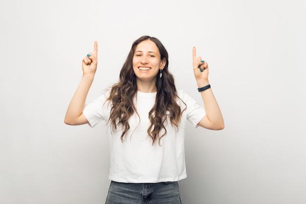 Retrato de jovem alegre e sorridente apontando para cima com as duas mãos