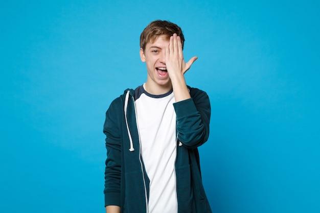 Retrato de jovem alegre em roupas casuais, cobrindo o rosto com a mão isolada na parede azul. emoções sinceras de pessoas, conceito de estilo de vida.