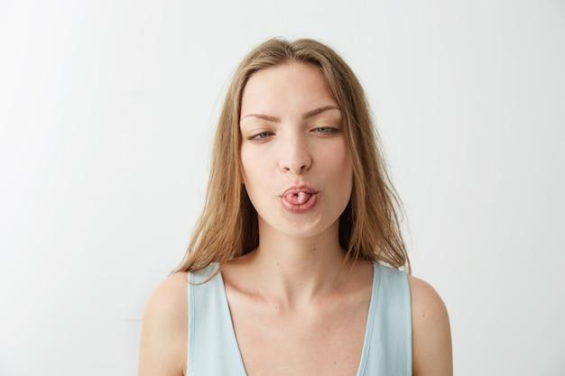 Retrato de jovem alegre engraçado mostrando a língua.