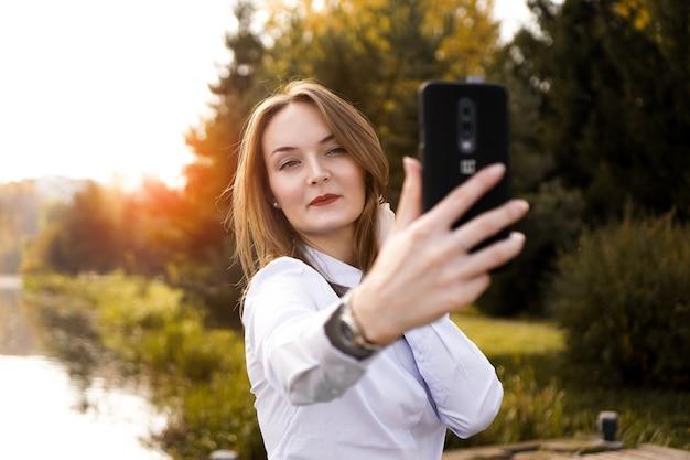 Retrato de jovem alegre fazendo selfie no parque