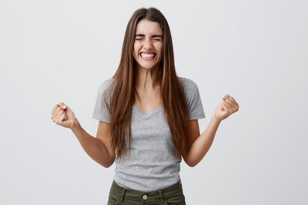 Retrato de jovem alegre feliz bela aluna com longos cabelos escuros na roupa cinza casual, sorrindo com dentes, espalhando as mãos com os olhos vestidos, sendo extremamente feliz, finalmente, conseguir papel no filme