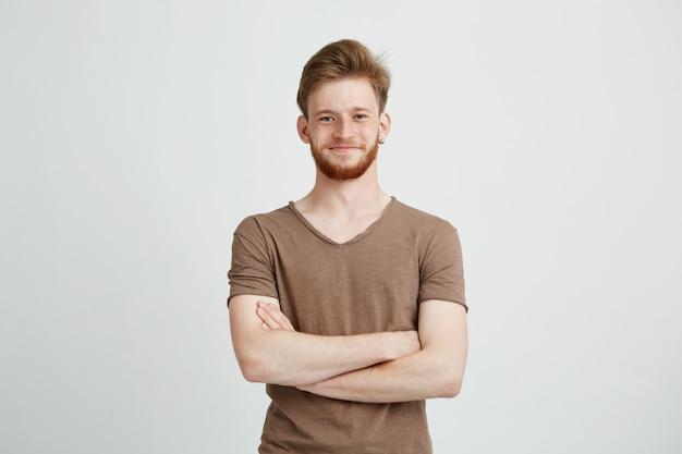 Retrato de jovem alegre feliz com barba sorrindo com braços cruzados.