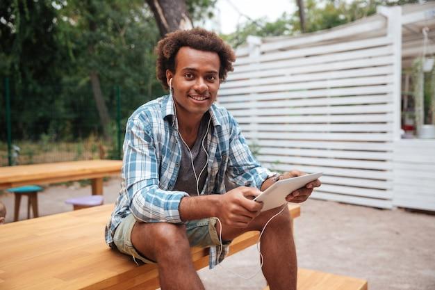Retrato de jovem alegre ouvindo música no tablet