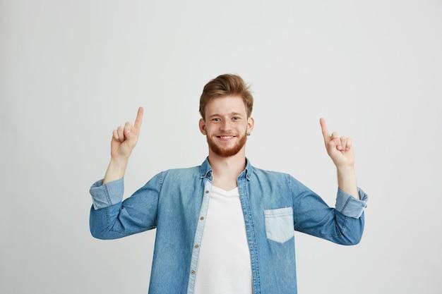 Retrato de jovem alegre sorrindo apontando o dedo para cima.