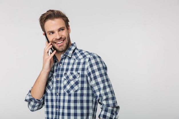 Retrato de jovem alegre vestindo camisa xadrez, sorrindo e falando no celular, isolado na parede branca