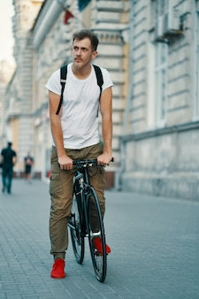 Retrato de jovem andando com bicicleta pensativamente clássica nas ruas da cidade