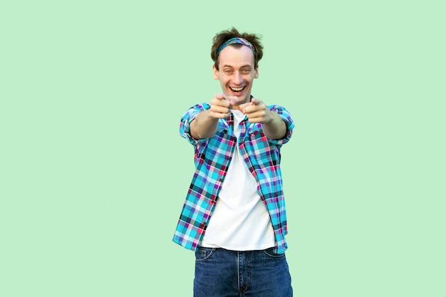 Retrato de jovem animado em casual camisa quadriculada azul e bandana em pé com um sorriso, olhando e apontando para a câmera. tiro de estúdio interno, isolado sobre fundo verde claro.
