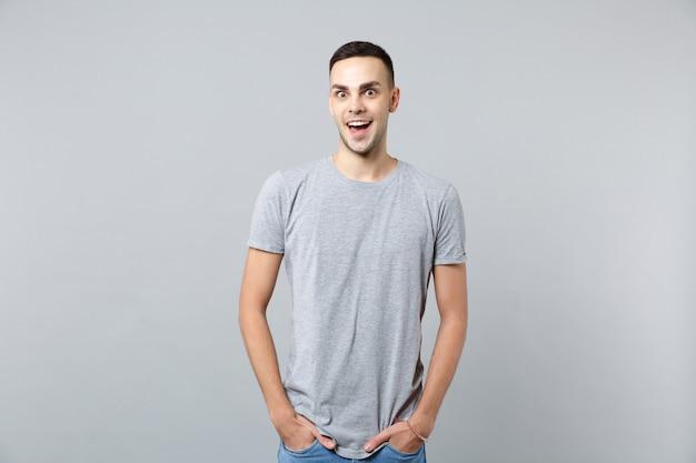 Retrato de jovem animado em roupas casuais, com a boca aberta e as mãos nos bolsos
