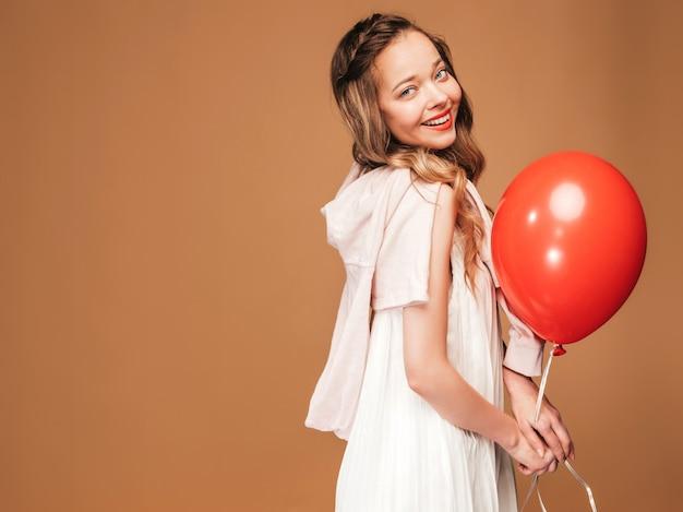 Retrato de jovem animado posando no vestido branco na moda verão. mulher sorridente com balão vermelho posando. modelo pronto para a festa