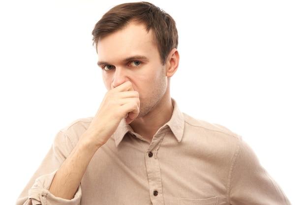 Retrato de jovem aperta o nariz e sente o cheiro ruim isolado no fundo branco do estúdio, halitose, conceito de suor fedorento