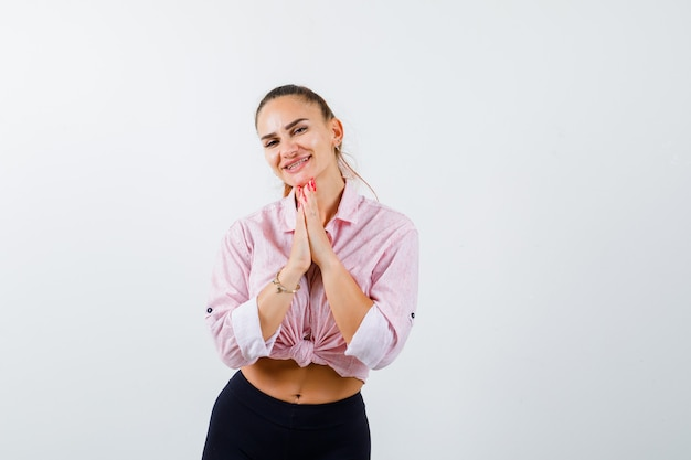 Retrato de jovem apertando as mãos em um gesto de oração na camisa