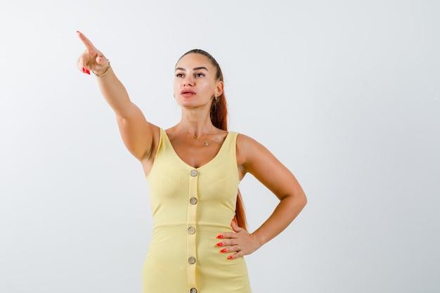 Retrato de jovem apontando para longe em um vestido amarelo e olhando para a vista frontal com foco