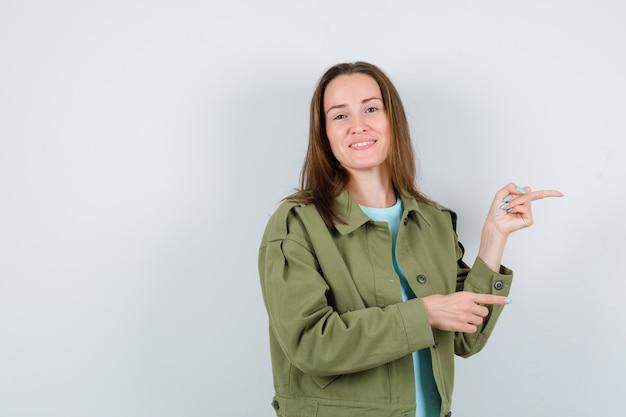 Retrato de jovem apontando para o lado direito em camiseta, jaqueta e olhando frontalmente feliz