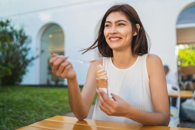 Retrato de jovem, aproveitando o tempo ensolarado enquanto toma um sorvete ao ar livre. conceito de estilo de vida.